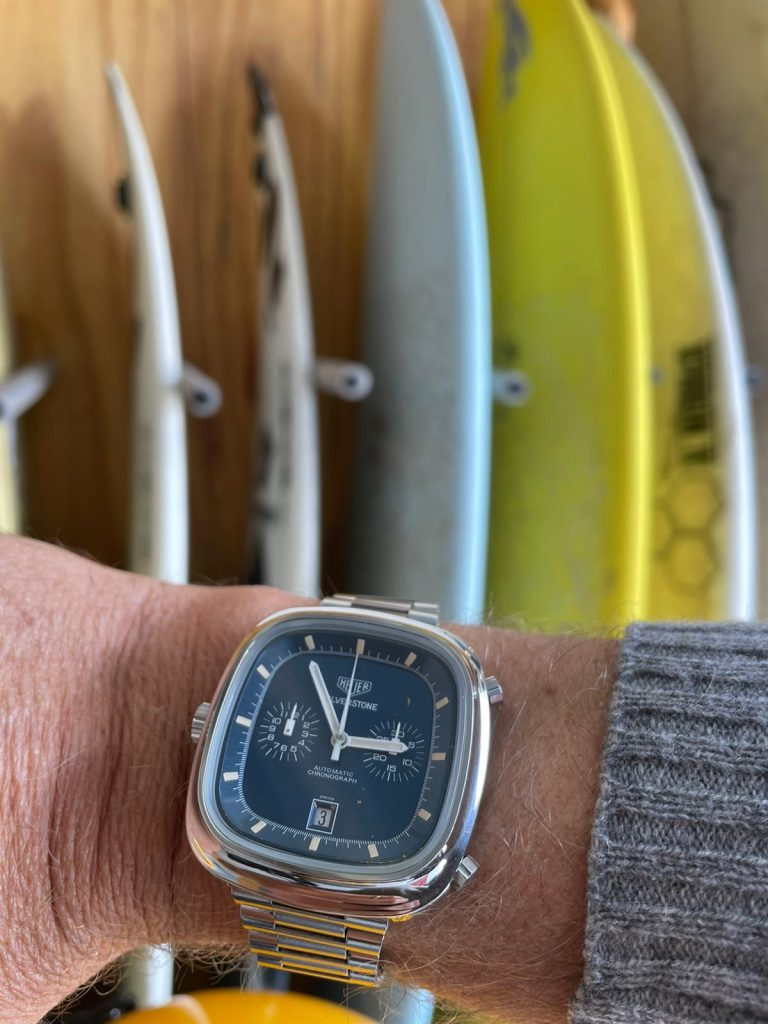 Vintage Auction Watch Heuer Silverstone On Wrist In Front Of Surf Boards