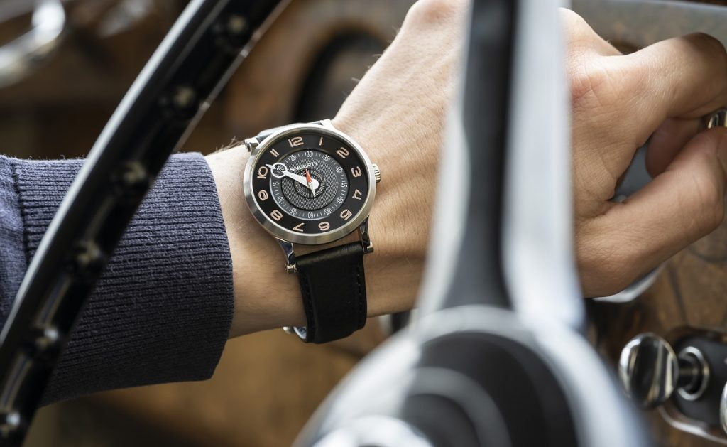 snglrty watch on the wrist of a gentleman driving a classic car